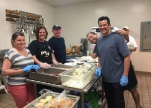 Adult volunteers cooking in the church kitchen