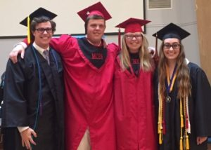 Four high school graduates in graduation gowns
