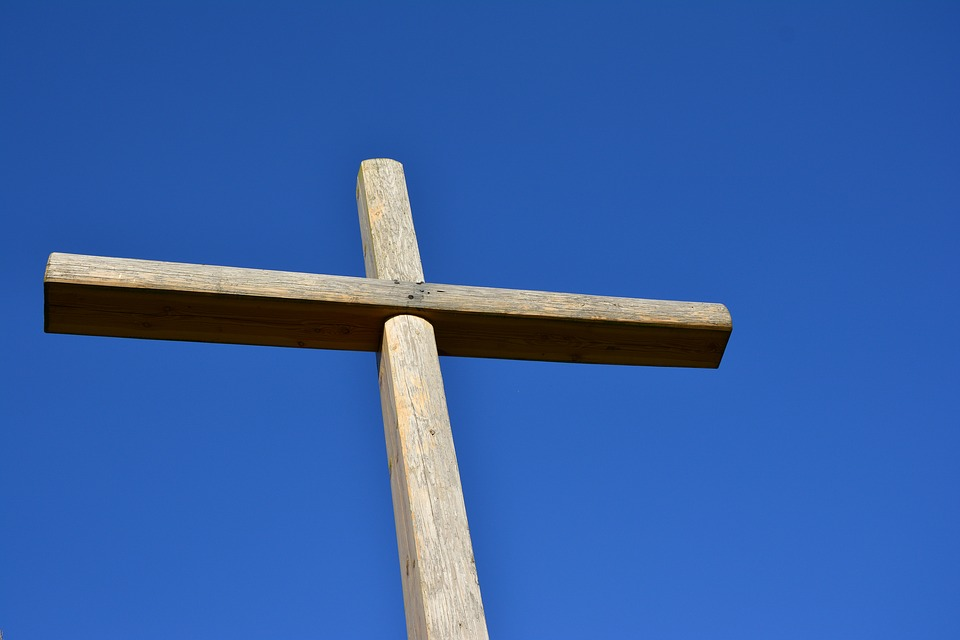 Rustic wooden cross against deep blue sky
