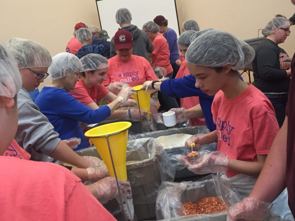 Volunteers of all ages wearing hairnets and packing meals