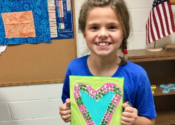 Girl holding painting of a heart